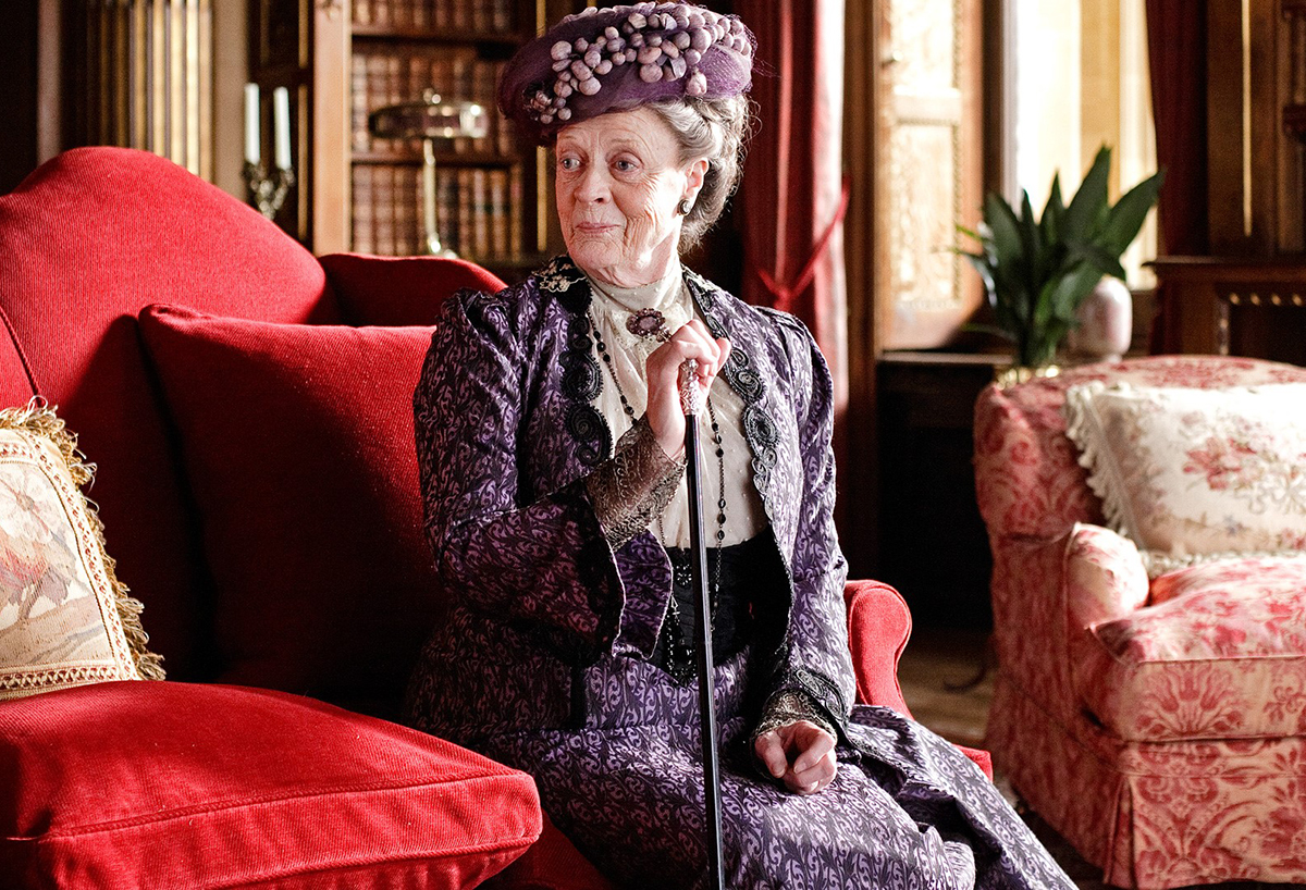 Dame Maggie Smith on the set of Downton Abbey, with armchair upholstered in Gainsborough's Medici design